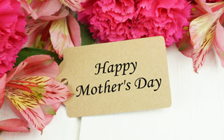 Happy Mother's Day gift tag close up with pink carnation and lily flowers against white wood background